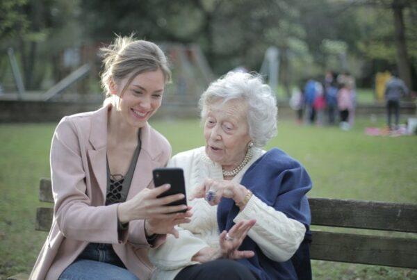 jonge vrouw laat oude vrouw iets zien op gsm, oude vrouw kijkt geboeid. - Het Schrijfpaleis
